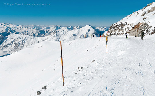 Wide view from piste of skier and snowboarder above Les Menuires