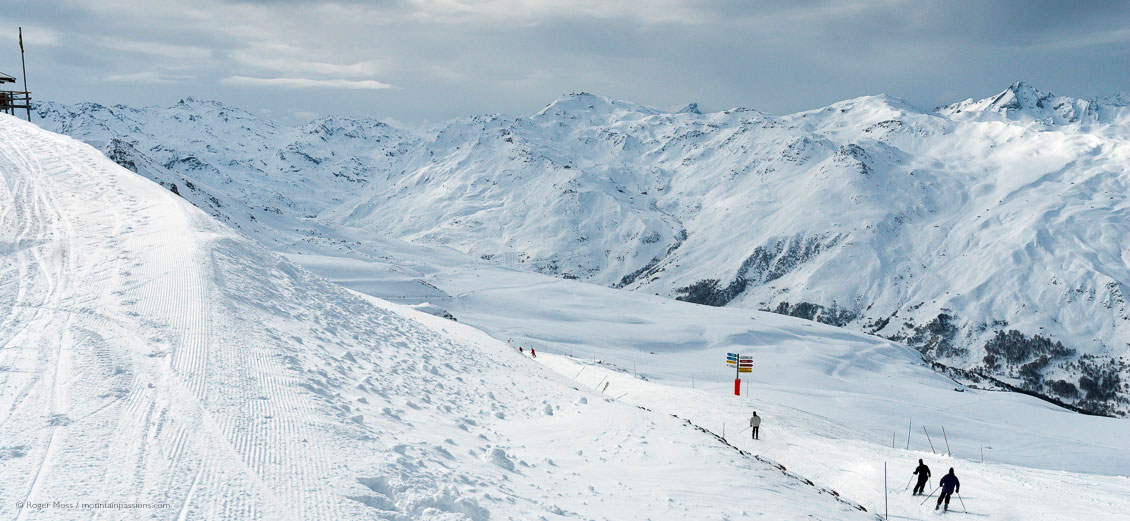 Wide overview of skiers setting off into big mountain landscape