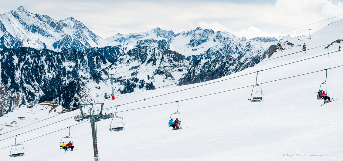 Wide view of skiers of 4-seat chairlift with mountain backdrop at Cauterets