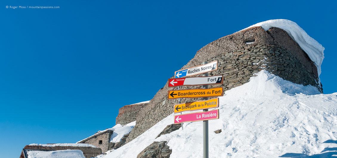 Low, wide view of ski piste sign with sow-covered fort above La Rosiere