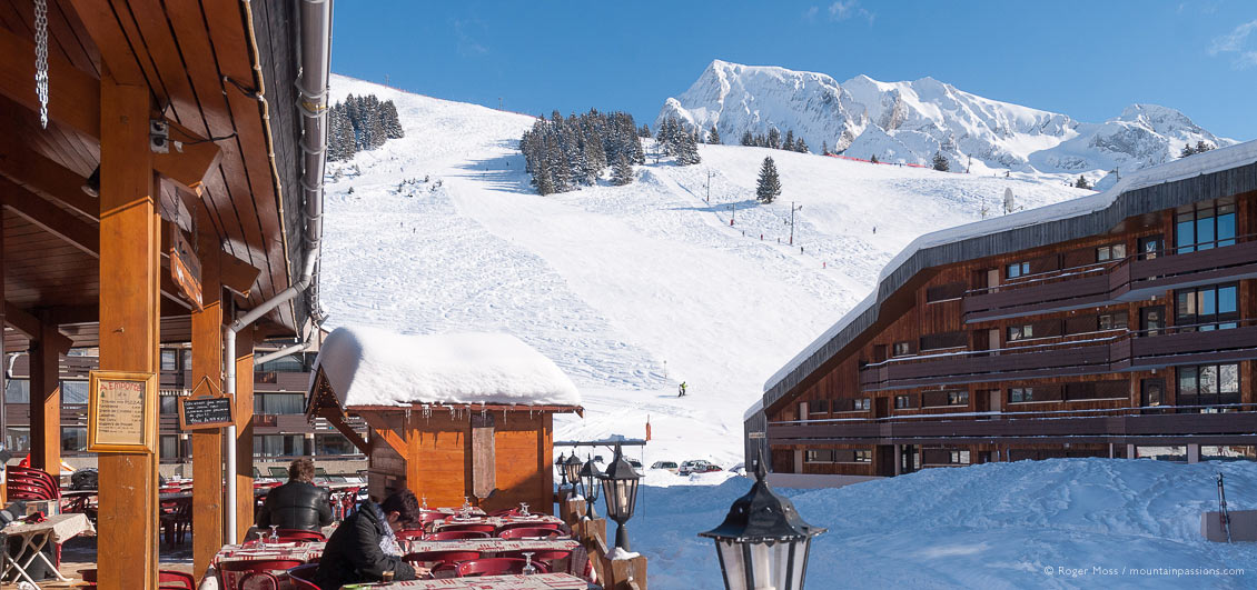 Wide view from restaurant terrace of mountain with skiers at La Clusaz