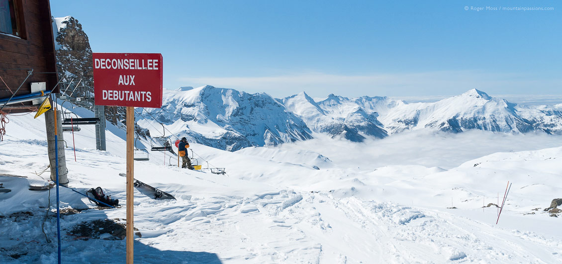 Wide view past piste signage to start of ski run, with snowboarder at Orcieres 1850