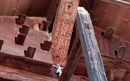 Detail of traditional Alpine chalet roof timbers with date inscription.
