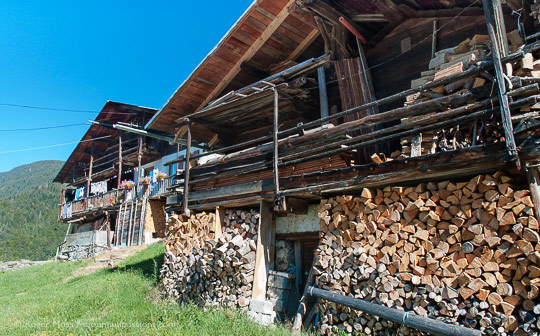 View past firewood stacked on front of grenier to traditional mountain chalet