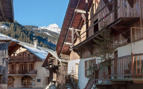 View through heart of village with renovated stone and timber chalets