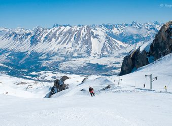 Skiers on piste with mountain views, Le Devoluy, southern French Alps