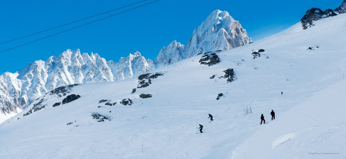 Skiers descending piste above Argentière, with snow-covered peaks in background.