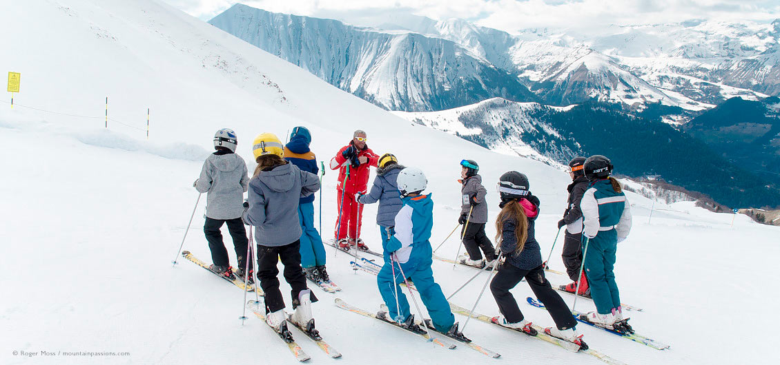 Skie instructor on mountainside with group of young skiers