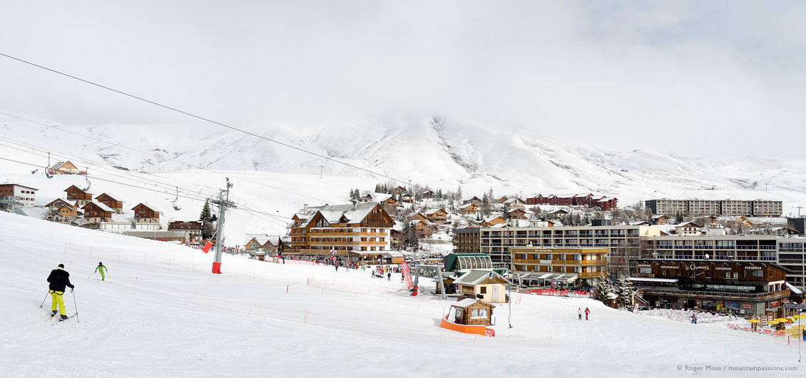 Wide view of skier returning to ski village of La Toussuire, Les Sybelles, Maurienne, French Alps.