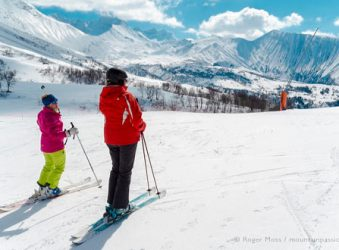 View of two skiers looking at spectacular mountain scenery
