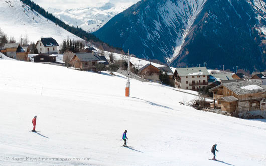 Skiers with instructor above traditional mountain village