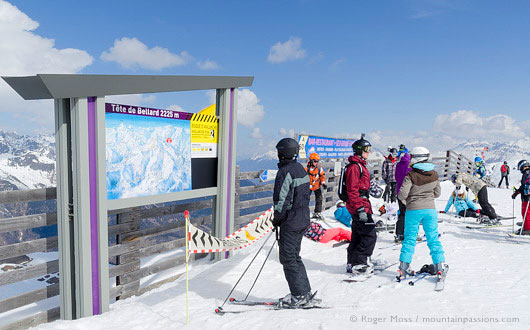Skiers looking at piste map sign beside chair-lift at La Toussuire, Les Sybelles, French Alps