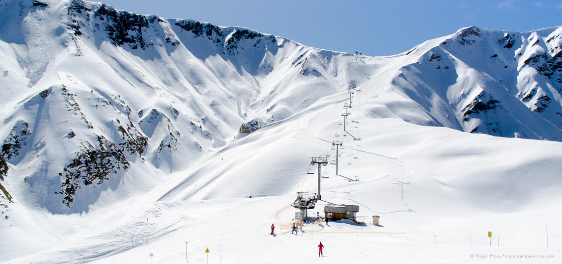 Wide view of skiers reaching chairlift, La Toussuire, Les Sybelles, French Alps