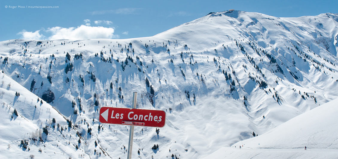 View past ski piste sign to mountainside with skiers at La Toussuire.