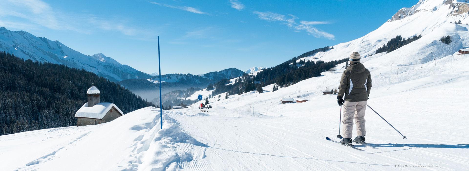 Low, wide view of skier in piste approaching mountain chapel