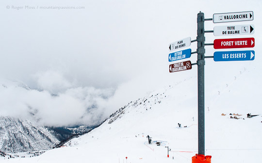 View past ski piste signage to snow-covered valley with clouds building