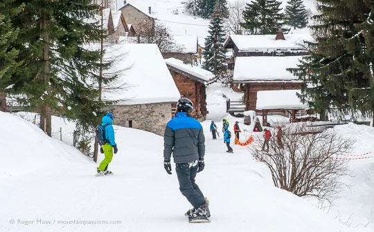 Rear view of snowboarders on piste into heart of Vallorcine