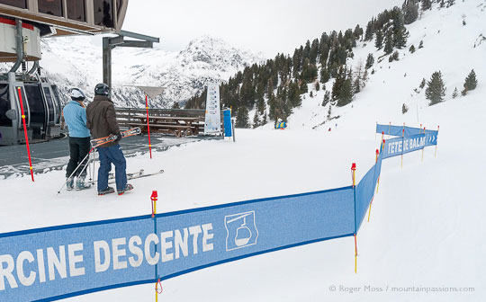 Wide view of two skiers beside top station of gondola ski lift, with piste signage above Vallorcine