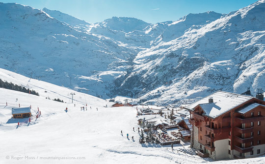 High view of snow-covered valley with mountain restaurant, ski apartments and skiers at Les Menuires