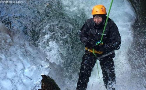 person abseiling down waterfall