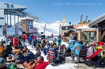 Skiers relaxing in mountain bar / restaurant terrace, above Les 2 Alpes