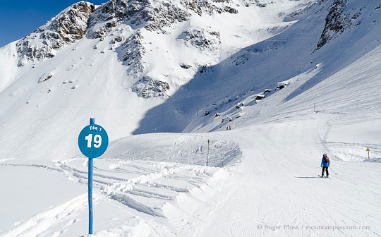 Skier on slow zone piste among wild mountain scenery at Les 2 Alpes
