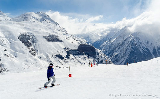 Wide view of snowboarder with valley, ski village and mountains at Les 2 Alpes