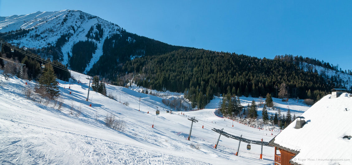 Wide view of ski lifts, pistes and mountains at Oz-en-Oisans