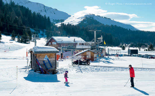 Young child on skis with father near ski lifts at Sommand, French Alps.
