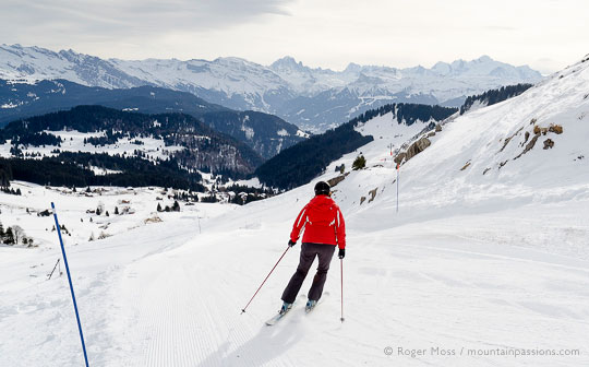 Skier on blue piste above Praz de Lys ski village, French Alps