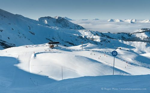 Wide overview of skiers, pistes and ski lifts above Chatel, Portes du Soleil, French Alps.