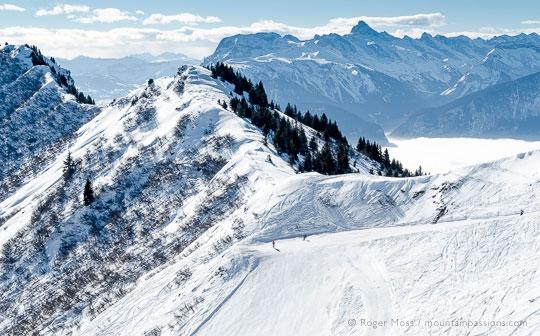 Skiers pausing on scenic piste at Praz de Lys, French Alps.