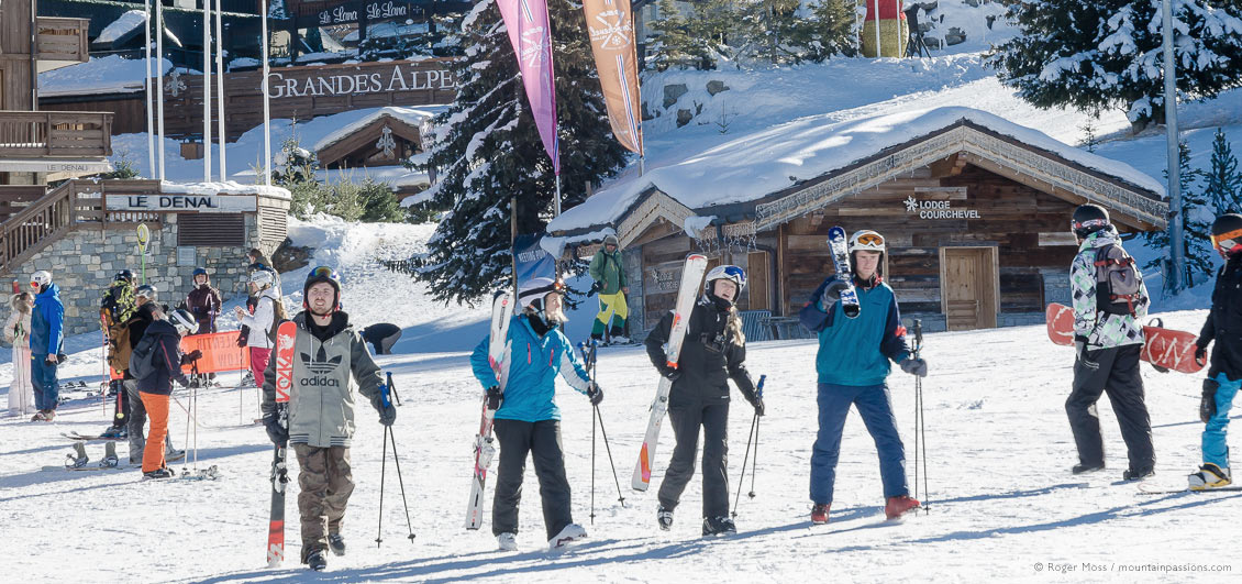 Skiers and snowboarder walking to ski lifts at Courchevel 1850