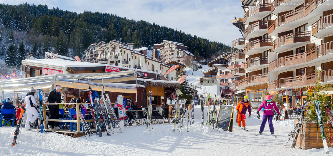 Wide view of skiers and restaurants at lunchtime in La Tania, French Alps.
