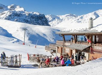 View of mountain restaurant, with skiers and snow-covered mountains above Courchevel Moriond, French Alps.