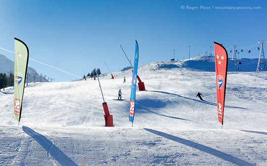 View from foot of pistes of skiers returning to Courchevel Moriond