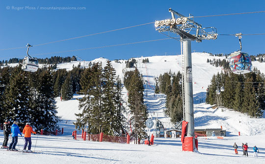 Skiers and gondola ski lift with mountainside at Courchevel, French Alps.