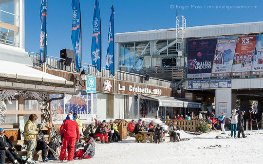 View of La Croisette, Courchevel, with skiers and ski instructor relaxing in the sun.