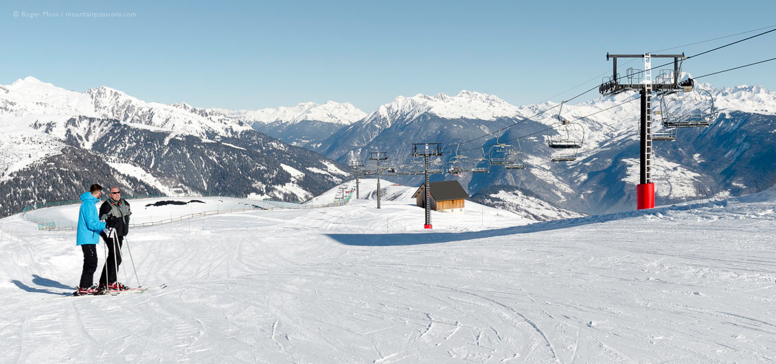Wide view of mountainside with skiers and chairlift at Valmorel