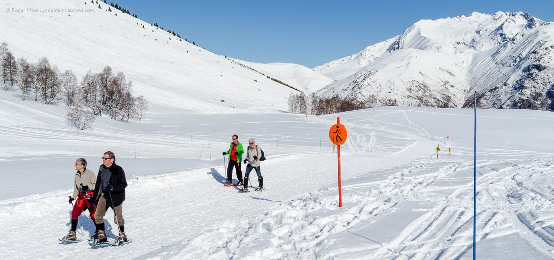 Wide view of two couples on snowshoe path at Les 2 Alpes, Isère, French Alps.