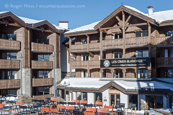 View across cafe tables to facade of Les Cimes Blanches Hotel and Apartments, Courchevel Moriond