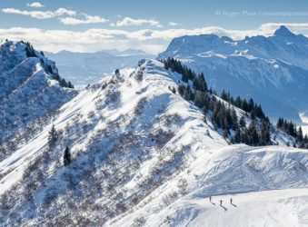 Wide overview of skiers on piste with big mountain views at Praz de Lys