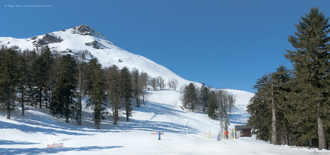 Piste with skiers and drag-lift at Hautacam, French Pyrenees