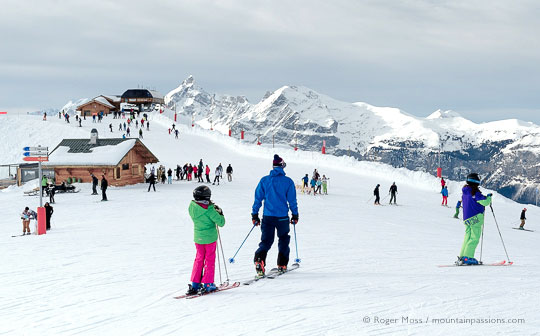 Wide view of skiers with chairlift and mountains, Grand Massif, French Alps