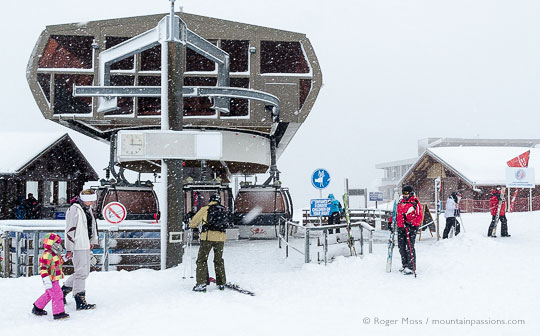 Skier beside gondola lift in falling snow at Samoens 1600, French Alps.
