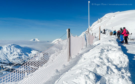 Skiers overlooking ski terrain from snow-covered ridge at Tete de Linga, Chatel