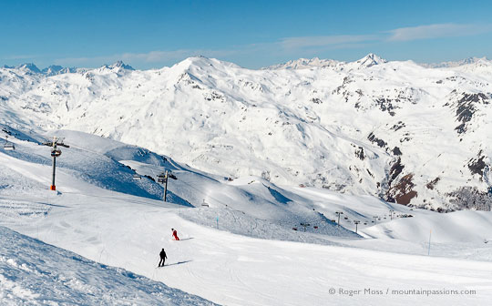 Skier and instructor on wide piste