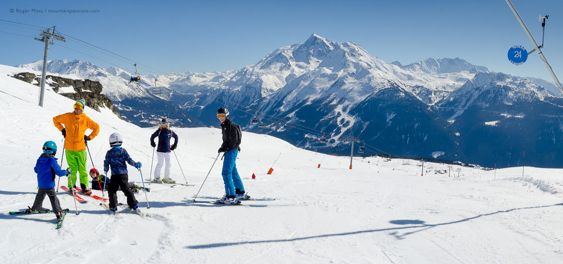 Wide view of family skers beside piste with chairlift and mountains at La Rosiere