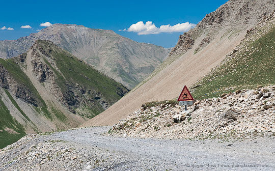 Wide view of mountain track with warning road sign and deep valley in background