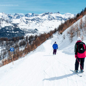 Two skiers on cruising piste at Vars, French Alps